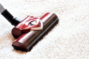 Vacuum cleaner. Close up of a modern hoover being used while vacuuming a woollen furry carpet.
